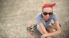 Portrait of a young woman with sunglasses, a red bandana and a longboard skatebo Stock Footage
