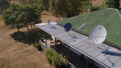 Domestic rooftop satellite dishes on rural Australia farm house version 2 Stock Footage