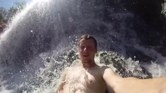 Male enjoying waterfall massage at Edith Falls in Nitmiluk NP Stock Footage