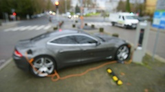 Electric car being charged in modern city view from above Stock Footage