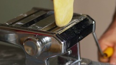 Rolling pasta dough in a pasta machine Stock Footage