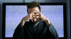 Bearded man in suit showing his eye in triangle with grainy screen behind him Stock Footage