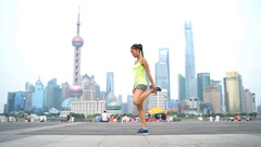 Runner stretching thighs after running workout in Shanghai China Stock Footage