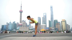 Fitness woman doing yoga in Shanghai city doing sun salutation Stock Footage