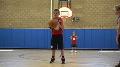 A boy shoots a free throw shot while playing basketball in an indoor gym. Stock Footage