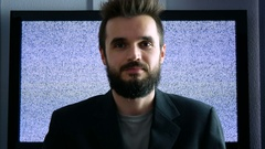 Happy bearded businessman moving forward and backwards with grainy screen behind Stock Footage