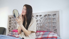 Beautiful woman holding a mirror and putting cream on face - make up concepts Stock Footage