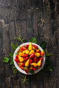 Top view of plate with orange, red and yellow hot chili peppers, greenery o.. Stock Photos