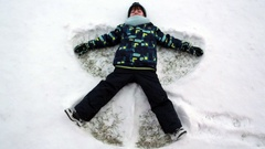 Little sweet child, boy, lying on north pole snow, making snow angel, winte.. Stock Footage