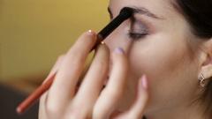 Makeup artist makes a girl beautiful makeup Stock Footage