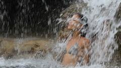 Waterfall with sexy woman in bikini bathing on travel Stock Footage