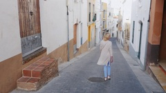 Young female tourist walks along the narrow streets of the old medieval town in Stock Footage