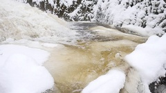 Frozen mountain stream. Snowy and icy fallen tree in chilly water. Stock Footage