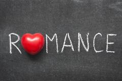 Romance word handwritten on chalkboard with heart symbol Stock Photos