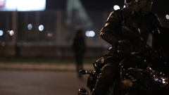 A sexy girl dressed in black leather walking towards a man on motorbike at night Stock Footage