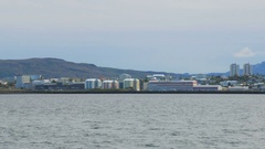 View of Reykjavik with modern buildings, moving cars, large mountain is on Stock Footage