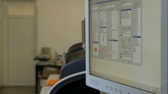 Entering information on monitor screen,worker for machine blurred by Pakito. Stock Footage