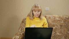 Woman aged carefully works at a laptop at home on the couch. She is typing on Stock Footage
