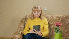 Woman aged resting at home on the couch for the Tablet PC. She leafs through the Stock Footage