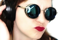 Woman with Headphones Listening Music, looking through glasses Stock Footage