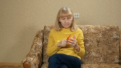 Women age eats fruit at home on the couch. She cuts off a piece of persimmon and Stock Footage