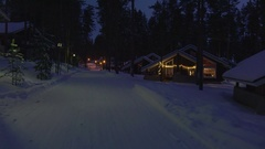 Moving at winter night by cozy wooden house in snowy forest village. Stock Footage