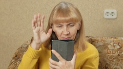 Senior woman with tablet sitting on couch in living room. Speaks video Stock Footage