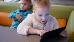 Cute kids boy and girl watch use tablet computer display sitting at cafe table Stock Footage
