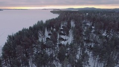 Aerial nordic winter landscape flying over snow forest village on lake shore. Stock Footage
