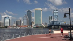 Joggers run with Jacksonville skyline in background, Florida, USA Stock Footage