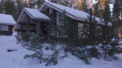 Moving at winter by cozy wooden house in snowy forest village at winter. Stock Footage