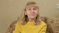 Women age she is smiling and looking at the camera while sitting at home on the Stock Footage