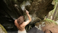 A man using a toothbrush to clean the holds before bouldering rock climbing up a Stock Footage
