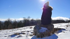 Girl with cap sitting on the stone on mountain during winter time with beautiful Stock Footage