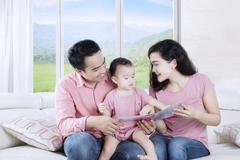 Asian parents reading story tale with daughter Kuvituskuvat