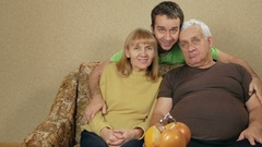 Young son of an elderly couple hugging at home on the couch. Everyone looks at Stock Footage
