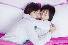 Mother and child sleeping together on bed Stock Photos
