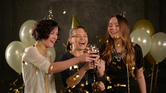 Three Women Clinking Glasses and Laughing Enjoy Birthday Party among Golden Stock Footage