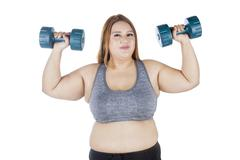 Overweight woman lifting dumbbell in hands Stock Photos