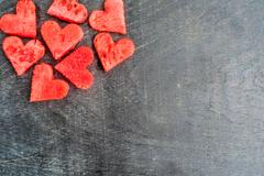 Watermelon hearts on the old wooden background. Flat lay Stock Photos