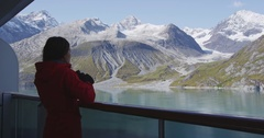 Tourist looking at Alaska Glacier Bay landscape using binoculars on cruise ship Stock Footage