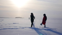 Two beautiful girls on the lake dabble in in the snow, jump, somersault, 4k Stock Footage