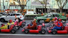 Young Japanese Go-cart drivers ride small spors cars at Shibuya in Tokyo, Japan Stock Footage
