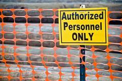 Bold warning on orange fence Stock Photos