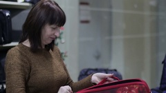 Woman chooses a laptop bag in a store Stock Footage
