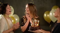 Two Women in Caps Singing Happy Birthday Song to Their Friend And Giving a Stock Footage