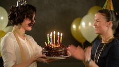 Birthday Girl Holding a Chocolate Cake with Candles and Trying to Bite off a Stock Footage