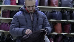 A person buys a travel bag in a store Stock Footage