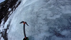 A man ice climbing with ice axes on a snow covered mountain, slow motion. Stock Footage