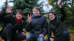 Three young positive male teenagers greeting say hello to the camera and Stock Footage